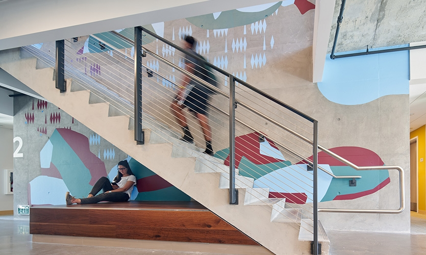 Three of the buildings have a stairway at the second and third floors along the mural wall, creating a connection between the two floor's sub-stories. (image: large mural of rocks on concrete stairwell)