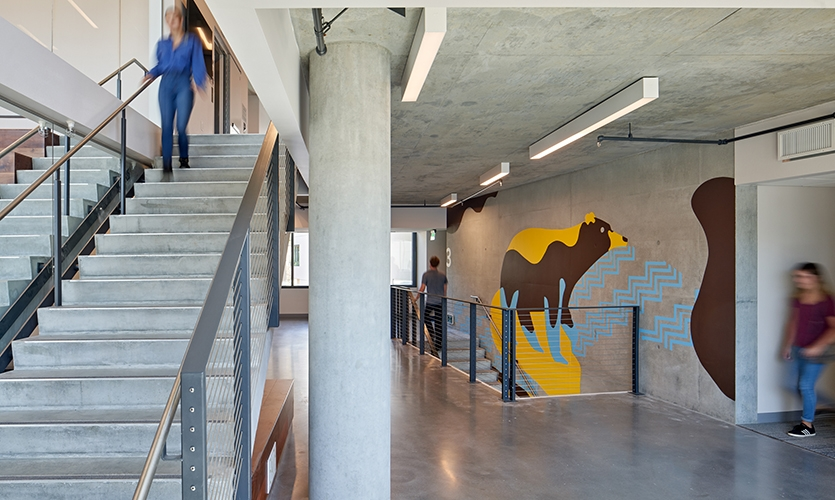 Artwork stacks vertically on each floor creating placemaking identity for residences. The Black bear influcenced the colors for tiłhini (San Luis Obispo) building (image: stairwell with bear wall)