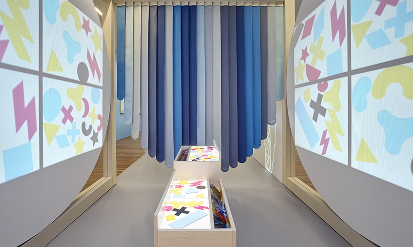 Composition Module: The larger projection increases a child's ability to understand scale, while making their creations visible to their parents and other visitors in the surrounding area. (image: colorful projections surround hanging fabric strips)