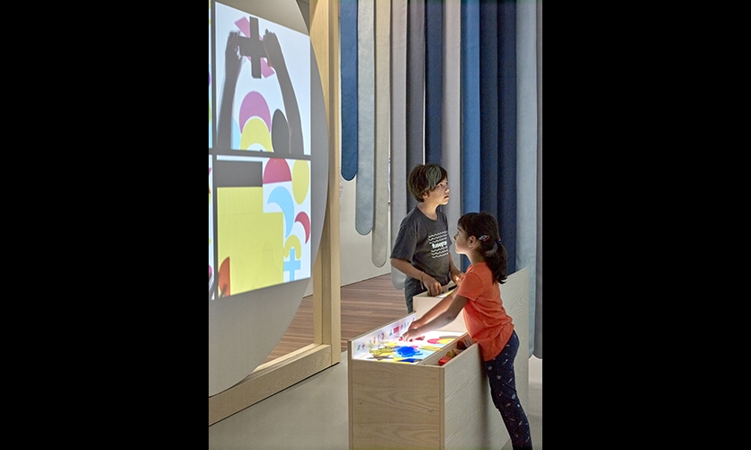 Light tables invite children to create a piece of art by using simple acrylic forms. As they work on the forms on backlit tables in front of them, the kids can see overhead projections of their design. (image: children at table)