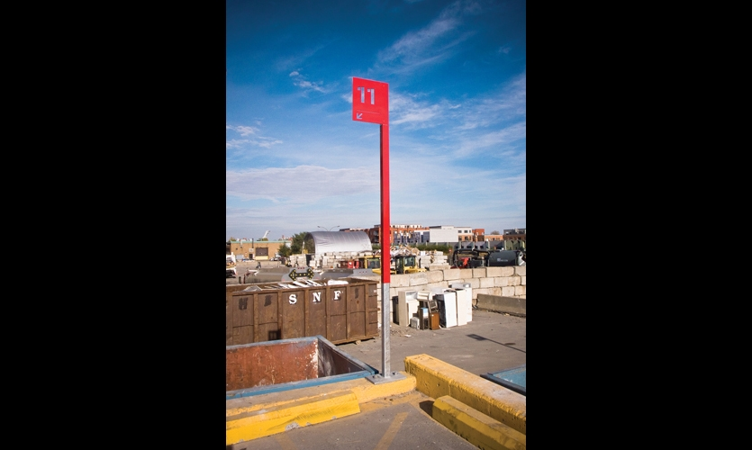 12-ft-tall, bright red mast signs with waterjet-cut numbers act as beacons, guiding users to designated drop-off areas.