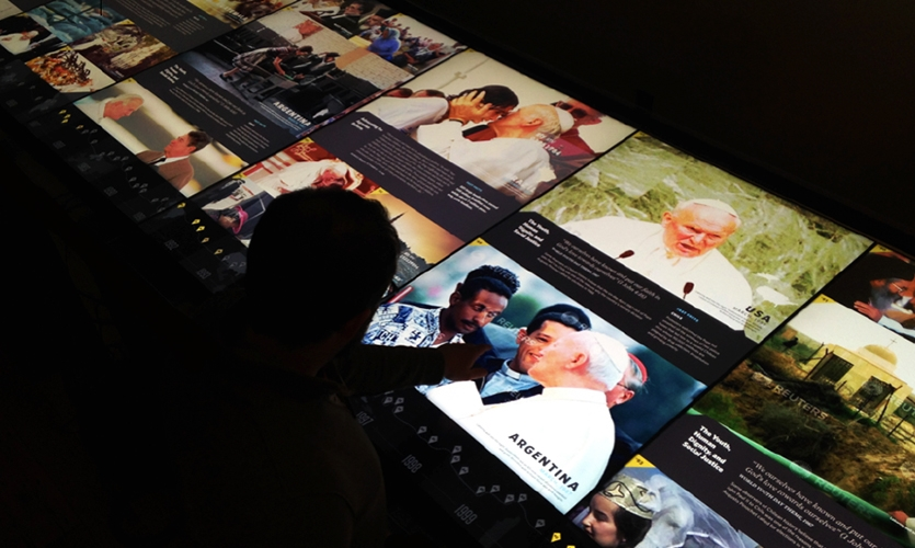 Visitors can step up to the nine-foot-long World Youth Day interactive table at the Saint John Paul II Shrine to virtually travel to the cities which have hosted these massive gatherings.