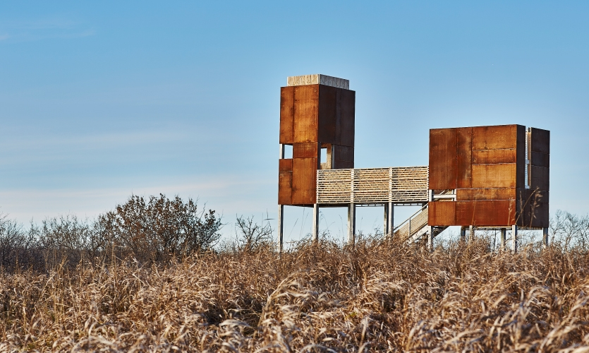 The platform's structure is composed of two open CORten steel chambers attached by a slatted cedar stage, all of which appears to float above the landscape.