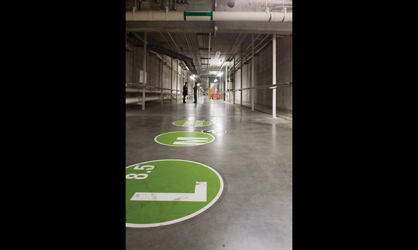 In the tunnels beneath the factory floor, the grid system continues with graphics stenciled on the concrete floors.