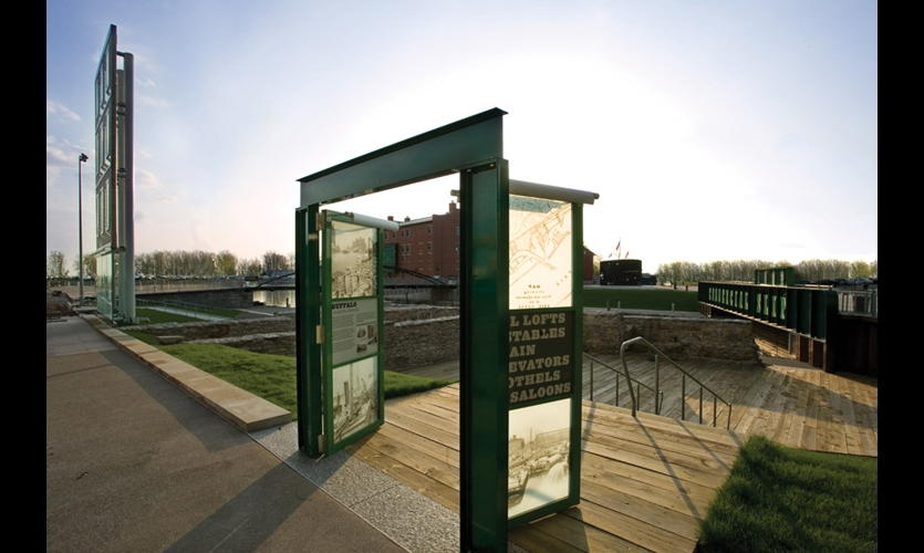 A ghostly portal overlooks the ruins of old canal warehouses. A steel door frame supports glass panels depicting scenes of the city during the canal's heyday.