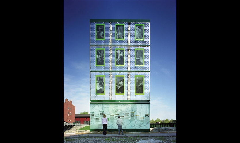 """An evocative 37-ft.-tall glass façade recalls the warehouses on Buffalo's bustling waterfront during the Erie Canal's heyday. The bottom third is a recreation of a 1908 canal surveyor's map. Above, enlarged vintage photographs mounted on a tracery of stainless steel """"bricks"""" project images of the tradespeople who would have occupied the warehouse lofts."""