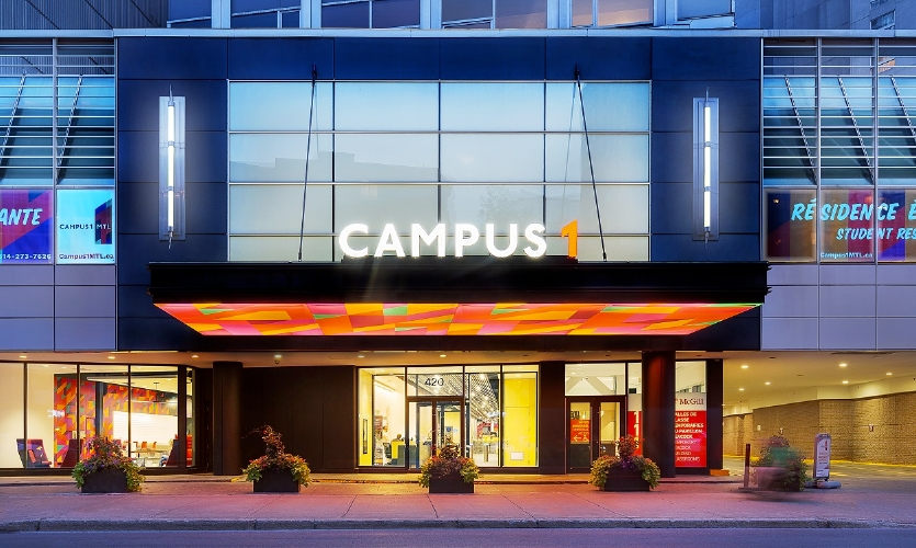 The front door of Campus1 MTL is set back from the curbside and a prominent canopy projects forward, displaying the bright faceted Montréal-themed pattern, illuminated on its underside