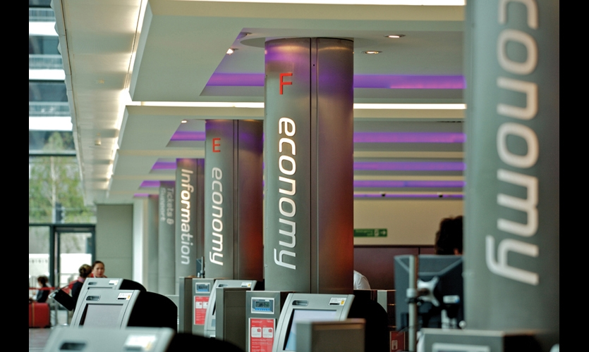 Support columns double as beacons guiding passengers to their appropriate check-in kiosks.