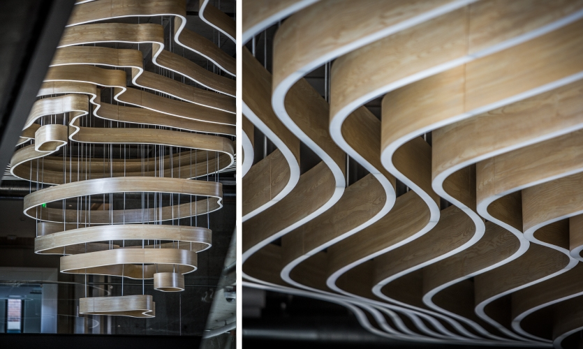 The thoughtful design and engineering also helped to both navigate a busy ceiling space and to conceal the attachments by way of custom paint and the emanating ring-like forms of the piece.