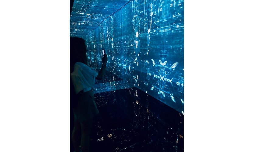 The Cyber Infinity experience is beautiful, scary and sure to be a social media smash hit. (image: visitor takes photo in immersive infinity mirrored room)