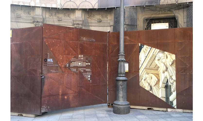 Construction Fence (Madrid): The Centro Canalejas building is being re-constructed, with a beautiful wrapper for the process. With rusted metal panels along the sidewalk, and a horizontal banner attached to the netting above.