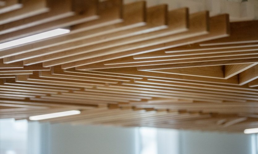 Oak Akan goldweight-derived patterns form the front of the entry desk and a drop ceiling that cleverly conceals mechanical systems, providing sound diffusion while communicating a message of a prosperous future.
