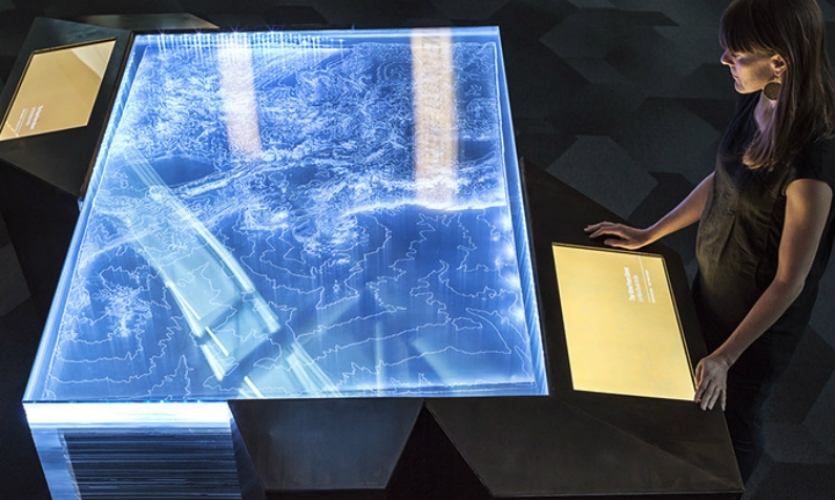 The exhibit's dramatic centerpiece is a topographic table made from layers of laser-etched acrylic. Visitors use touchscreens to explore Colorado ecosystems.