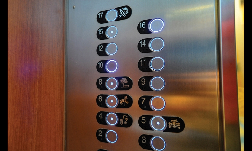 Elevator buttons incorporate neighborhood symbols (e.g., a tree for Central Park) to make wayfinding more intuitive, while a blue ring of light makes the buttons pop.