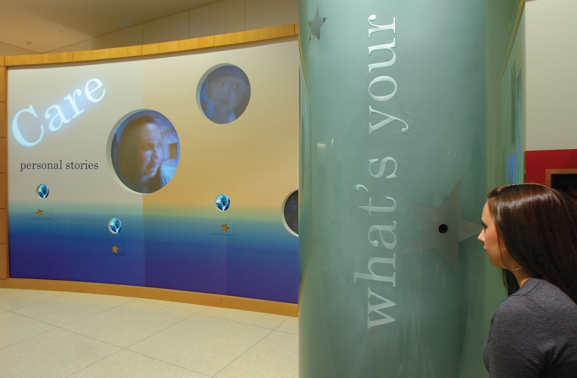 A column in the center of the space was a potential barrier, but designers turned it into an asset by making it glass and using it as a viewing portal to tell the hospital's most important stories.