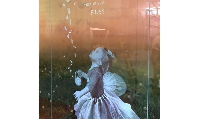 "In the center of the installation, a small child has been etched into the crystal glass shown magically releasing a flight of dozens of butterflies, fireflies and swirling leaves from her ""Jar of Possibilities."""