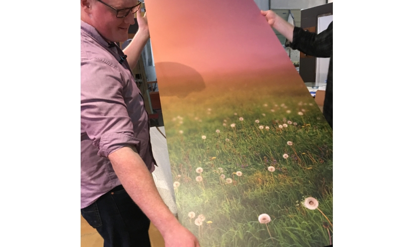 Studio staff review the finely printed dibond art backer in-studio for any necessary last minute changes before installation.