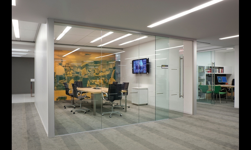 Design360 enlivened employee spaces such as this pantry with digital murals using archival newsroom images. The images are screened onto glass in colors corresponding to finishes on various levels. (Photo: ©Albert Vecerka/Esto)