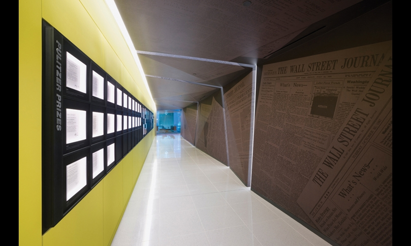 Quiet hallways were designed as a retreat from the hectic newsrooms. Here, The Wall Street Journal's Pulitzer Prizes are displayed in a gridded framework of blued steel, with captions sandblasted into the metal. Wrapping the opposite wall, polyester fabric wallpaper is printed with front-page coverage of major news events. (Photo: ©Albert Vecerka/Esto)