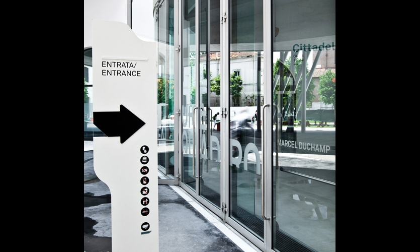 The sign system is a spare palette of black and white, with wave-cut shapes, embossed arrows, and cuts in the structure.