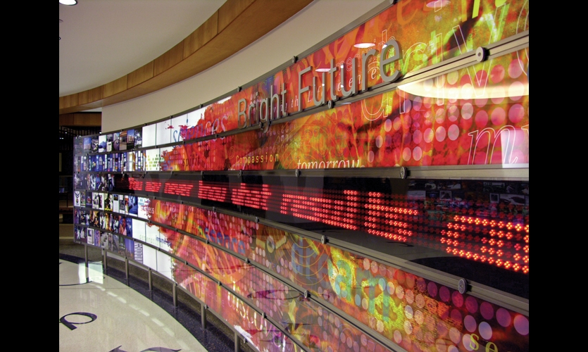 An open, elliptical space celebrates the company's past, present, and future. Curved, 40-ft. panels integrate bands of backlit photo images, dimensional letters, and an LED strip that scrolls inspirational quotes.