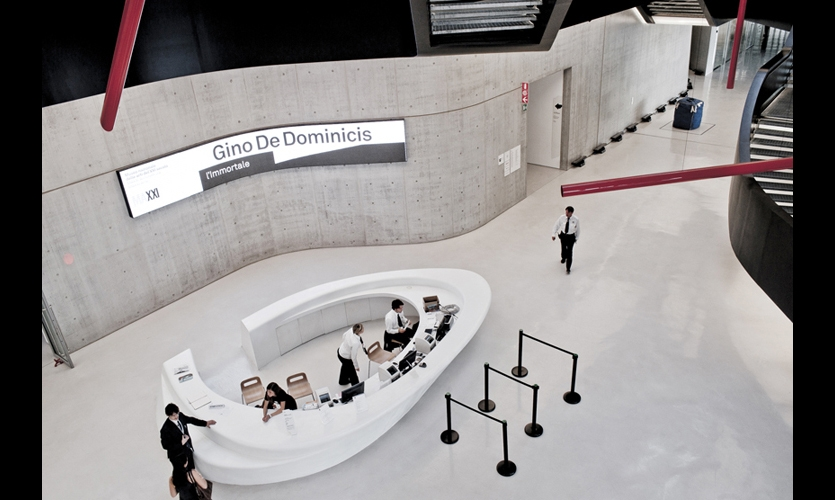 A subtly bent LED screen curves with the concrete wall above the reception desk and provides information about current exhibits and upcoming events.