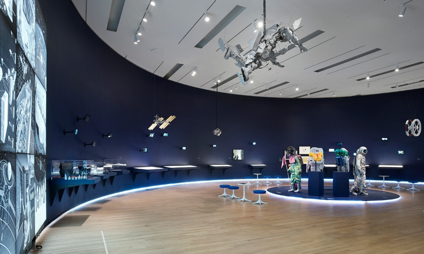 "The low-lighted gallery was transformed into a nearly semicircular shape, lined with ""control center"" cases and a constellation of differently sized small monitors."