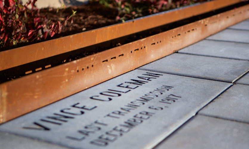 As visitors move into the center of the plaza, low to the ground on the west-facing side of the carillon is a brick commemorating Vince Coleman's last telegraph transmission.