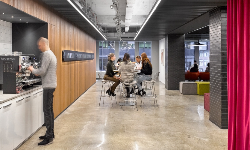"In the Work Café area, employee engagement and connection is showcased in the ""Gensler people wall."""