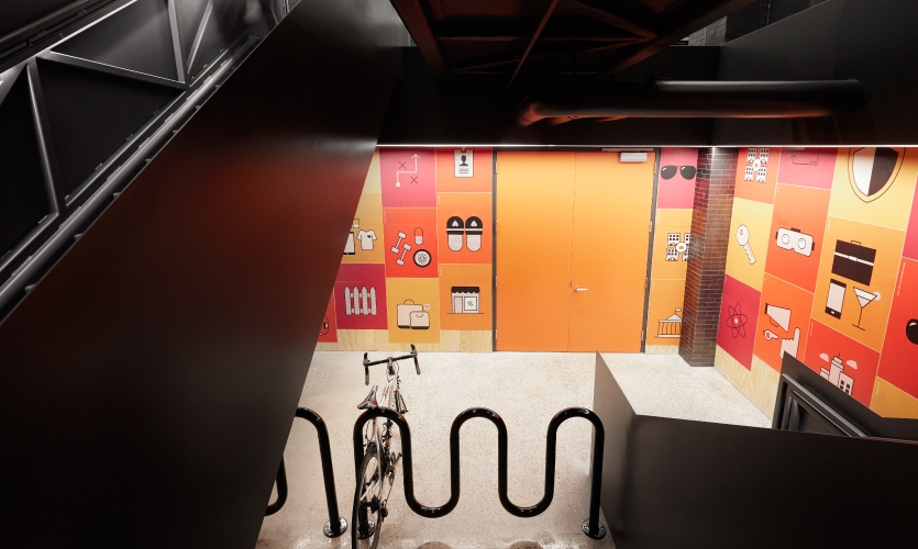 An art space has been covered in gold, orange and red wheat-pasted posters emblazoned with illustrations of Gensler's 31 practice areas.