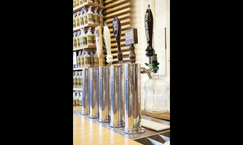 """At the store's """"Reduce, Reuse, Recycle, Refill"""" cleaning bar, bar tap handles with custom-designed labels pour no-VOC cleaners into re-usable containers."""