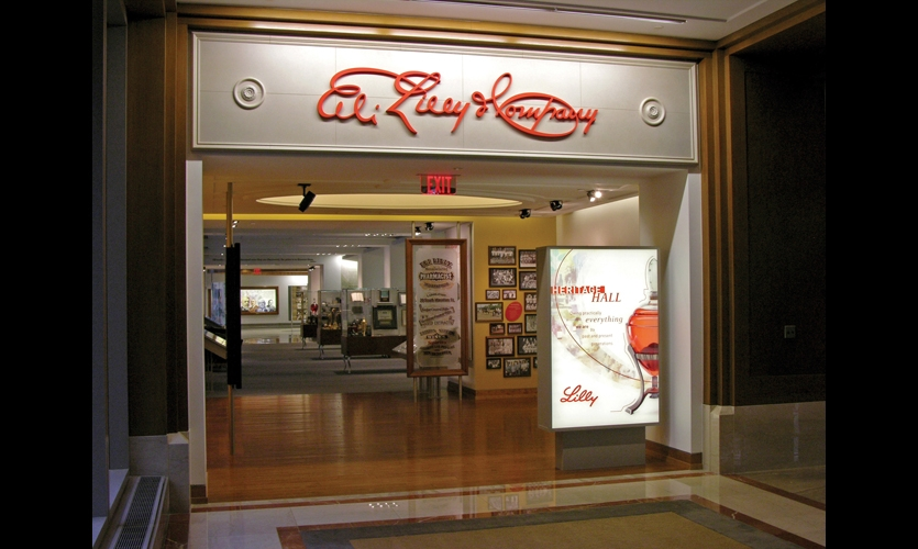 The storefront-like entry to the Lilly Heritage Hall is capped by a keystone recalling an existing building's original facade with an early version of Eli Lilly's signature. Double-sided light boxes punctuate the space.