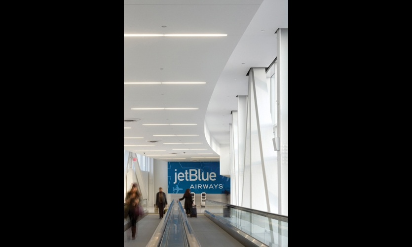It's a long walk down the 700-ft.-long skybridge connecting the terminal with mass transit. A cheerful JetBlue wall mural is both wayfinding cue and brand message. (Photo: Nic Lehoux)