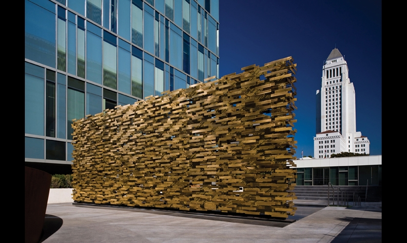 Over 12 ft. high by 32 ft. long and 11,000 pounds, the porous brass wall scatters the Los Angeles light against its many metal surfaces.