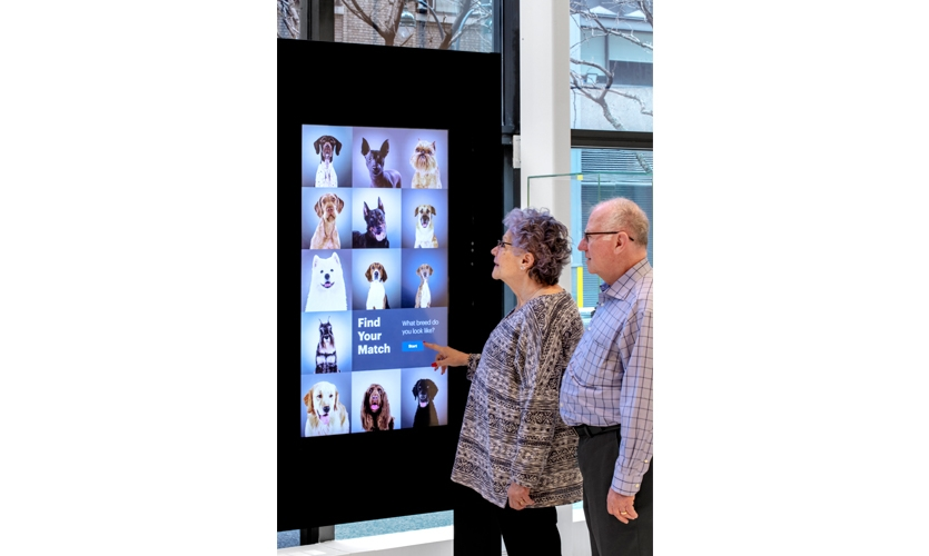 """The """"Find Your Match"""" kiosk that takes your photo, aligning its likeness with an AKC-registered dog breed. (image: two people interact with kiosk)"""