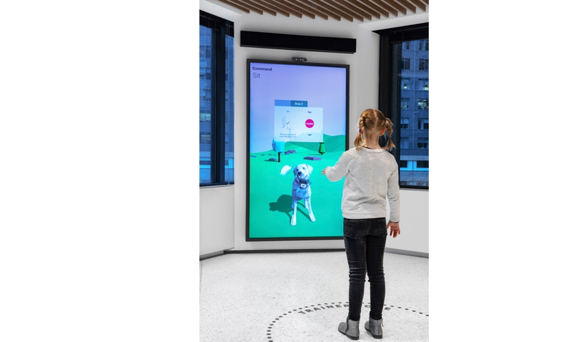 """The """"Train a Dog on the Job"""" exhibit teaches visitors how to train a virtual dog with voice commands and hand signals. (image: girl interacts with virtual dog)"""