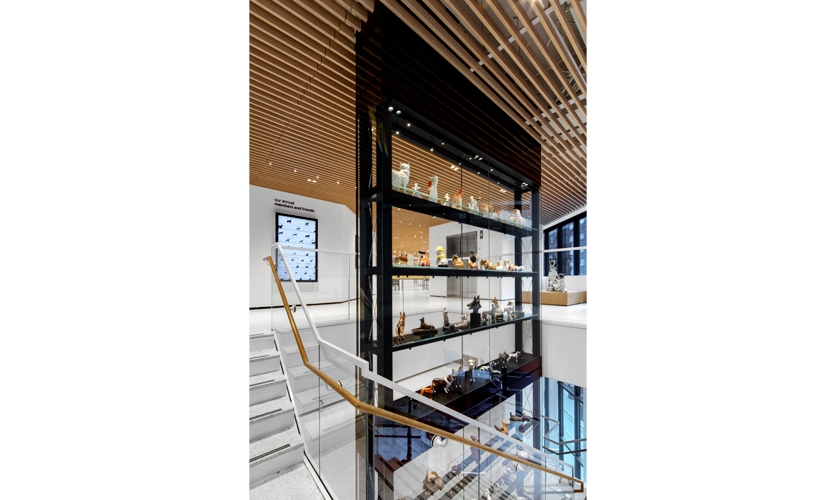 Three-dimensional objects are encased in an engaging 34-foot-tall glass vitrine in the center of a winding stair. (image: large vitrine with artifacts)