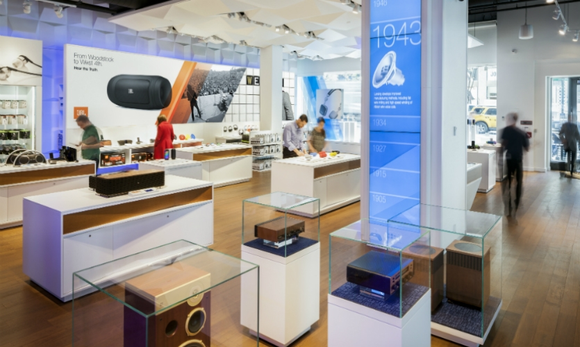 """As a backdrop to product displayed in museum-like vitrines, """"brand billboards"""" graphically tell the Harman story."""