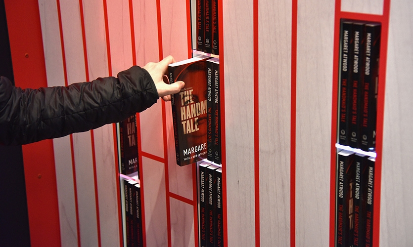 The display houses paperback copies of the book that passersby can take down to reveal powerful messages of resistance from the novel.