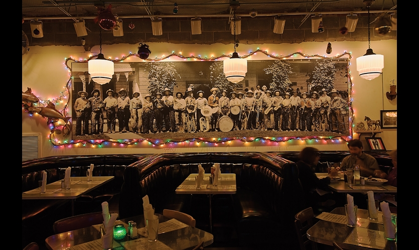 Bob Wade's mural at the Rancho 616 steakhouse plays on the universal fascination with cowboys. Wade says he'd rather perpetuate myths about the West than participate in its homogenization.