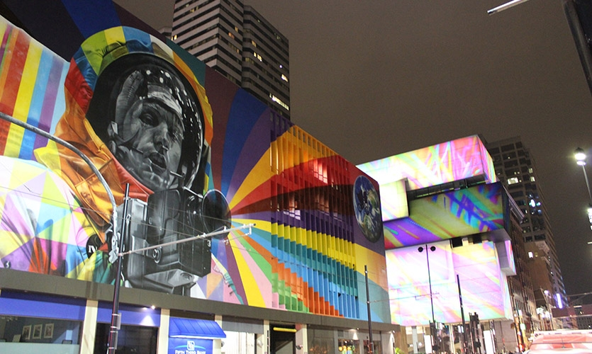 View of CAC projection mapping behind Eduardo Kobra's mural