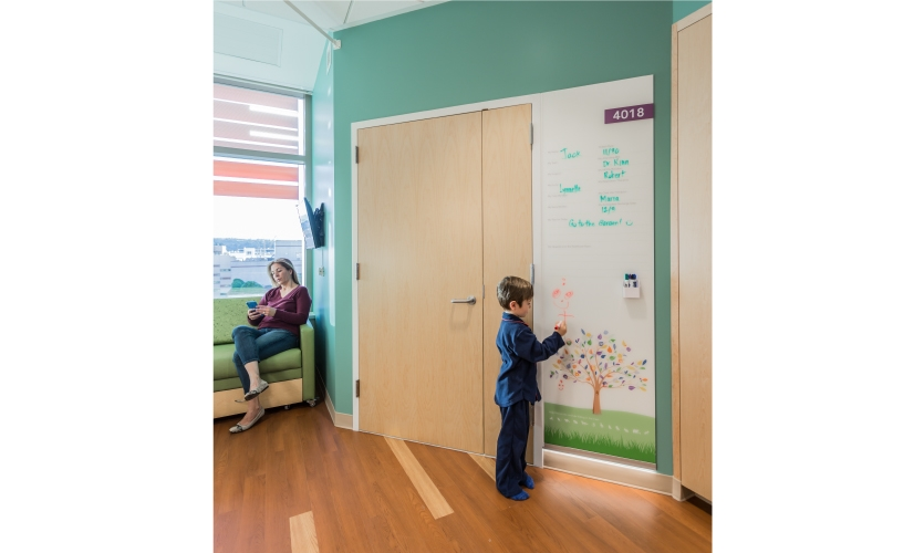 . Inside, the room there is a large custom glass (dry erase) panel that displays patient team info and goals for the day. (image: child using dry erase puzzle board, photo by Emily Hagopian)