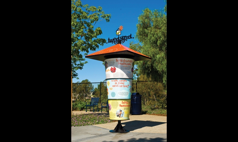 The birdhouse-inspired interpretive kiosk features three conical aluminum panels, with graphics embedded in high-pressure laminate. Two of the three panels spin, but the third is stationery and embedded with Braille text.