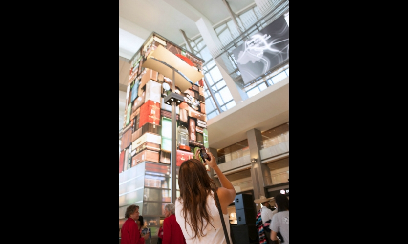 Here, it takes the form of the classic kitschy luggage tower found at many airports. The tower's base of diffused glass is an interactive surface that responds to the gestures of passersby by triggering real-time visual effects.