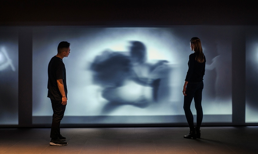 Projected figures emerge magically from the shadows into light.