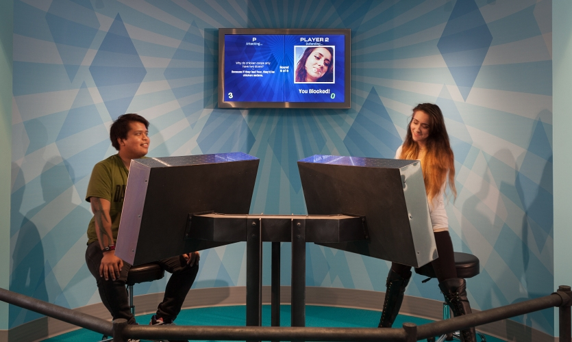 The Laugh Battle setup consists of two touchscreens with cameras and a video display behind that shows the scoring so the audience can follow along.