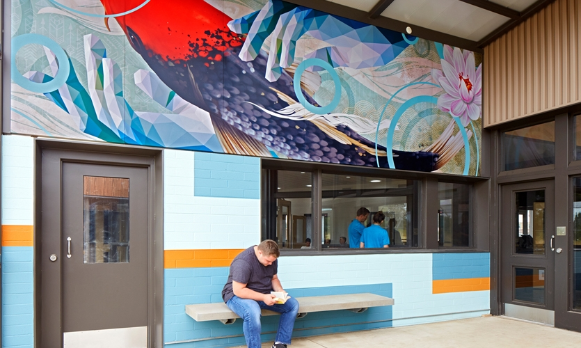 The artwork is printed on durable powder-coated metal panels with concealed fasteners for safety. Easy-to-maintain painted patterns extend the energy across the courtyard wall.