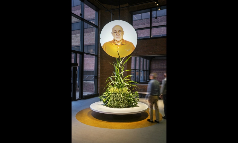 At the end of the exhibit, a video of Monsanto's head of research welcoming visitors is rear-projected onto an 8-ft.-diameter, ceiling-hung acrylic disk. The planter below is a changeable bouquet of crops grown at Monsanto's greenhouses.
