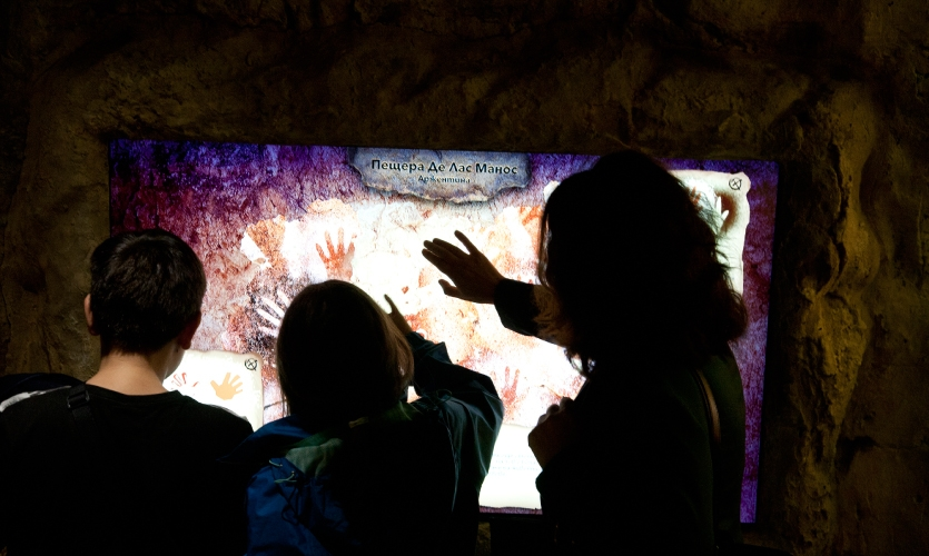 A group of children explore a cave painting digital interactive.
