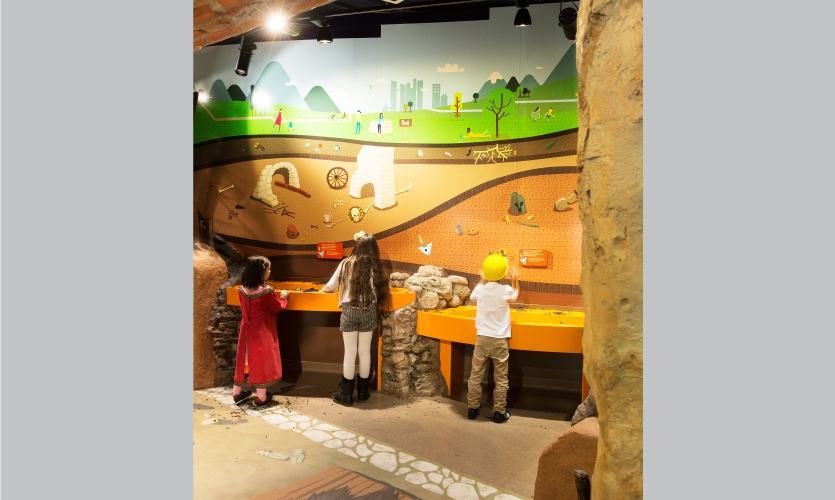 Children enjoy the murals and interactive learning stations in the underground/archaeology exhibit.